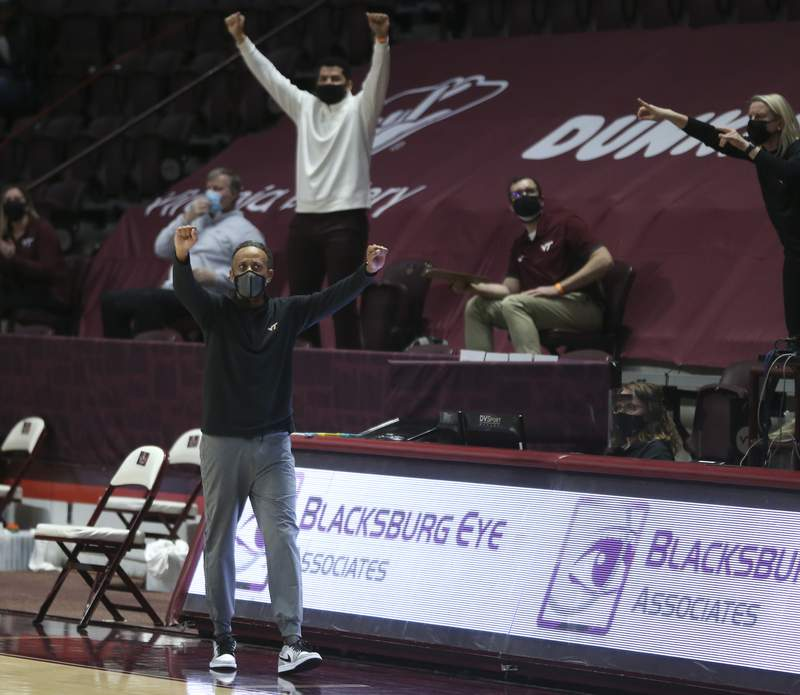Virginia Tech head coach Kenny Brooks  and his bench celebrate a score during the first half of an NCAA college basketball game in Blacksburg Va. Sunday February 28 2021. (AP Photo /  MATT GENRTY, The Roanoke Times, Pool)