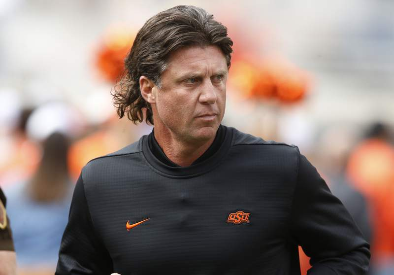 FILE - In this Oct. 6, 2018, file photo, Oklahoma State football coach Mike Gundy runs onto the field before the team's NCAA college football game against Iowa State in Stillwater, Okla. Mike Holder, Oklahoma States athletic director, said late Thursday, July 2, 2020, an internal review had found no sign or indication of racism in the football program under Gundy after a number of players raised concerns. (AP Photo/Sue Ogrocki, File)