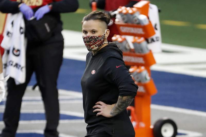 FILE - In this Dec. 20, 2020, file photo, San Francisco 49ers offensive assistant Katie Sowers stands on the field during warmups before an NFL football game against the Dallas Cowboys in Arlington, Texas.  Sowers will not be returning to the 49ers in 2021 after becoming the first female coach to make it to the Super Bowl last year. A person familiar with the situation said the 34-year-old Sowers will leaving coach Kyle Shanahans staff where she worked closely with receivers coach Wes Welker. The person spoke on condition of anonymity because the team had not made an announcement. (AP Photo/Roger Steinman, File)