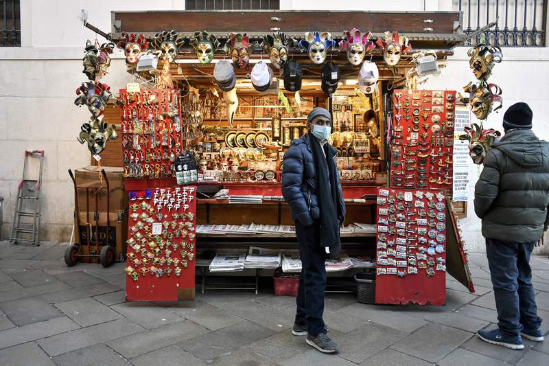 A vendor wearing a face mask stands by a stall in Venice, Italy, Friday, Feb. 28, 2020. Authorities in Italy decided to re-open schools and museums in some of the areas less hard-hit by the coronavirus outbreak in the country which has the most cases outside of Asia, as Italians on Friday yearned for a return to normal life even amid fears that the outbreak could plunge the country's economy into recession. (Claudio Furlan/Lapresse via AP)