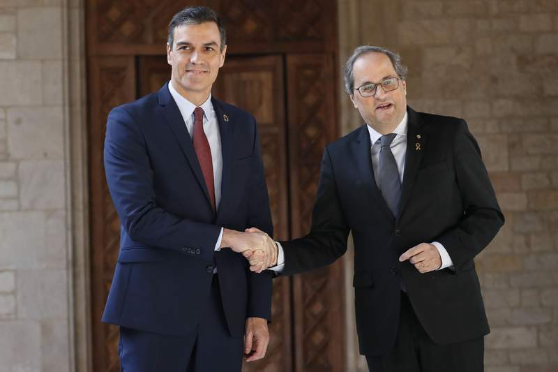 Spanish Prime Minister Pedro Sanchez, left, shakes hands with Catalan regional President Quim Torra at the Palace of the Generalitat, the headquarter of the Government of Catalonia, in Barcelona, Thursday, Feb. 6, 2020. (AP Photo/Emilio Morenatti)