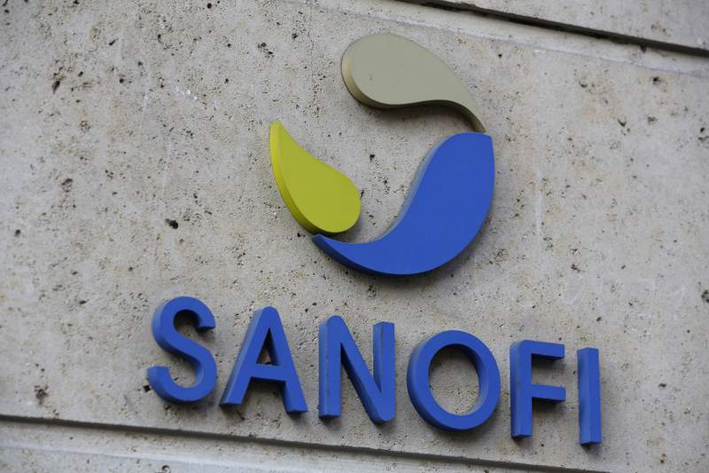 """This photo taken taken Monday Nov.30, 2020 shows the logo of French drug maker Sanofi at the company's headquarters, in Paris. Drugmakers GlaxoSmithKline and Sanofi say their potential COVID-19 vaccine won't be ready until late next year as they seek to improve the shot's effectiveness in older people. The companies said Friday that early-stage trials showed the vaccine produced an """"insufficient"""" immune response in older adults, demonstrating the need to refine the product so it protects people of all ages (AP Photo/Thibault Camus)"""