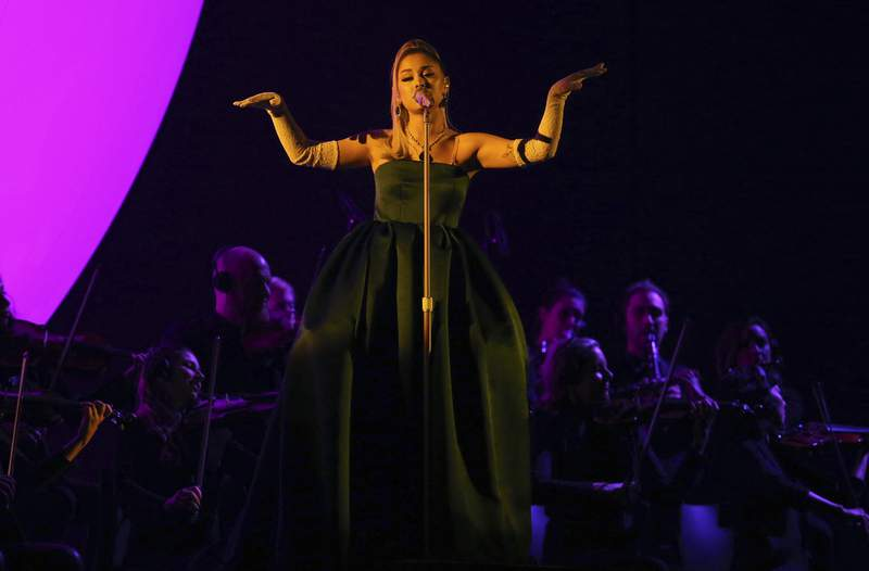 FILE - In this Sunday, Jan. 26, 2020, file photo, Ariana Grande performs a medley at the 62nd annual Grammy Awards in Los Angeles. On Sunday, Dec. 20, 2020, Grande announced she is engaged in a series of social media photos of her and her fiance, Dalton Gomez, and a massive engagement ring. (Photo by Matt Sayles/Invision/AP, File)