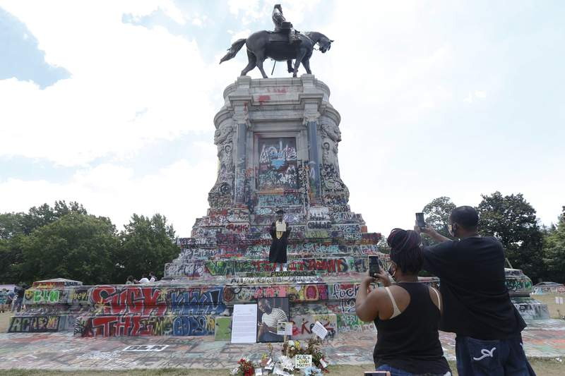 EDS NOTE: OBSCENITY - The parents of King William High School 2020 graduate Lance Jennings, center, take photographs of him on the statue of Confederate General Robert E. Lee on Monument Avenue Wednesday June 24, 2020, in Richmond, Va. The statue has become a focal point of protests for the Black Lives Matter movement in the Richmond area. (AP Photo/Steve Helber)
