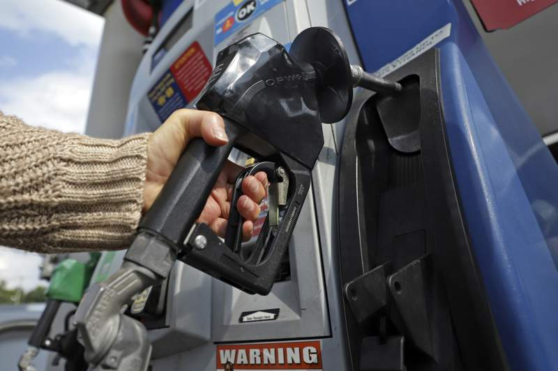 FILE - In this Monday, Sept. 16, 2019, file photo, a woman pumps gas at a convenience store in Pittsburgh. Industry analyst Trilby Lundberg of the Lundberg Survey said Sunday, March 15, 2020, that gas prices could continue to fall as demand shrinks amid the coronavirus pandemic. (AP Photo/Gene J. Puskar)