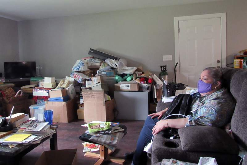 In this photo taken Thursday, Oct. 8, 2020, Houston resident Alice Torres sits inside her home, which had been damaged during Hurricane Harvey in 2017. Torres says she has not unpacked boxes of belongings in her living room because she is still waiting for help from a city program to finish repairs in her home. This week, the state of Texas took over the program over what it says is slow progress the program has made in repairing homes. Torres and other residents who have applied for assistance say they're worried the takeover could lead to more delays. (AP Photo/Juan A. Lozano)