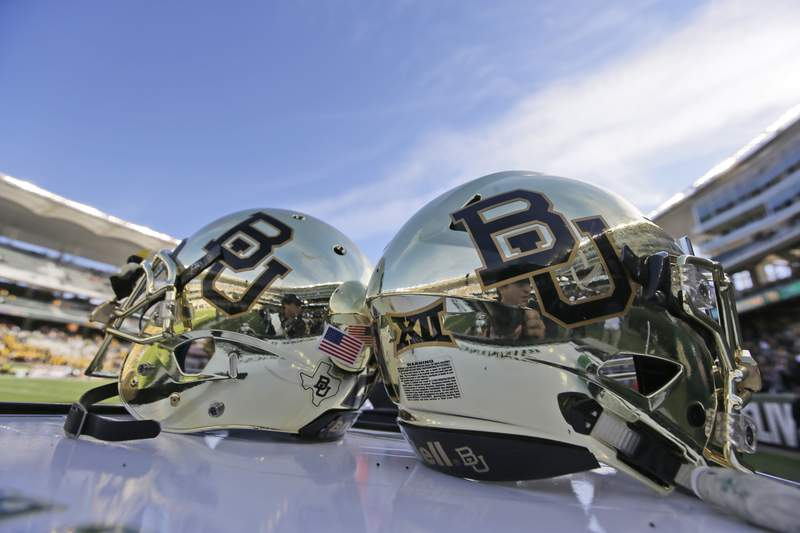 FILE - In this Dec. 5, 2015, file photo, Baylor helmets on shown the field after an NCAA college football game in Waco, Texas. The NCAA infractions committee said Wednesday, Aug. 11, 2021, that its years-long investigation into the Baylor sexual assault scandal would result in four years probation and other sanctions, though the unacceptable behavior at the heart of the case did not violate NCAA rules.(AP Photo/LM Otero, File)