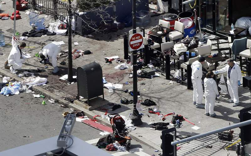 FILE - In this April 16, 2013, file photo, investigators examine the scene of the second bombing outside the Forum Restaurant on Boylston Street near the finish line of the 2013 Boston Marathon, a day after two blasts killed three and injured more than 260 people. The Biden administration's argument at the Supreme Court for reinstating the death penalty for convicted Boston Marathon bomber Dzhokhar Tsarnaev hinges on keeping evidence from the jury that prosecutors themselves relied on at an earlier phase of the proceedings. (AP Photo/Elise Amendola, File)