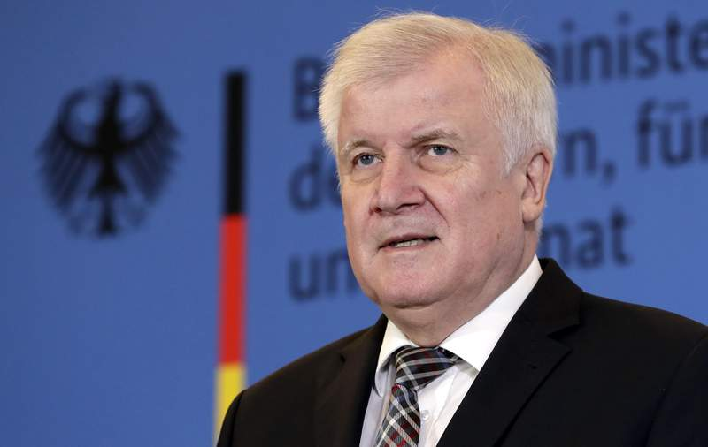 FILE -- In this Monday, Nov. 5, 2018 photo German Interior Minister Horst Seehofer addresses the media during a press conference in Berlin, Germany. Police have raided homes in three German states after the German government banned a far-right group, the interior ministry said. Whoever fights against the basic values of our free society will get to feel the resolute reaction of our government, Interior Minister Horst Seehofer said. There's no place in this country for an association that sows hatred and and works on the resurrection of a Nazi state. (AP Photo/Michael Sohn, file)