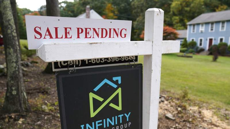 FILE - In this Sept. 29, 2020 file photo, a sale pending sign is displayed outside a residential home for sale in East Derry, N.H. Sales of previously occupied U.S. homes rose in July for the second month in a row, though they only increased modestly from a year ago, suggesting the red-hot housing market may be cooling off a little. Existing homes sales rose 2% last month from June to a seasonally-adjusted annual rate of 5.99 million units, the National Association of Realtors said Monday, Aug. 23, 2021. (AP Photo/Charles Krupa, File)