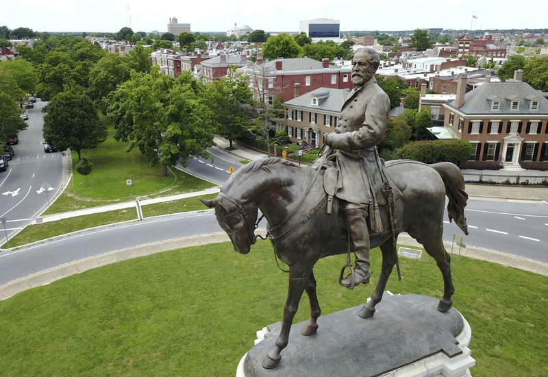 FILE - This June 27, 2017, file photo, shows the statue of Confederate General Robert E. Lee that stands in the middle of a traffic circle on Monument Avenue in Richmond, Va.  A lawsuit seeking to prevent Virginia Gov. Ralph Northams administration from removing an enormous statue of Gen. Lee can proceed, a judge ruled Tuesday, Aug. 25, 2020, clearing the way for a trial in the fall. (AP Photo/Steve Helber, File)
