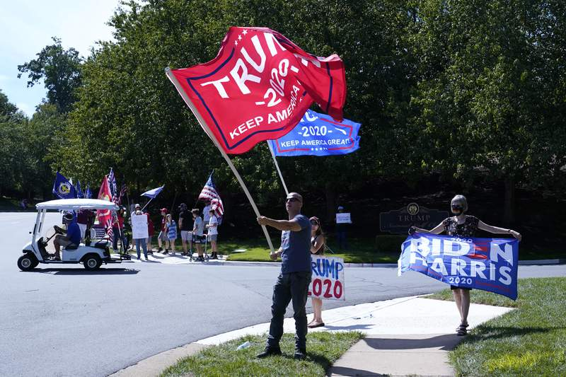 Protesters and supporters of President Donald Trump gather outside Trump National Golf Club in Sterling, Va., Saturday, Sept. 5, 2020, before the departure of Trump's motorcade. (AP Photo/Patrick Semansky)