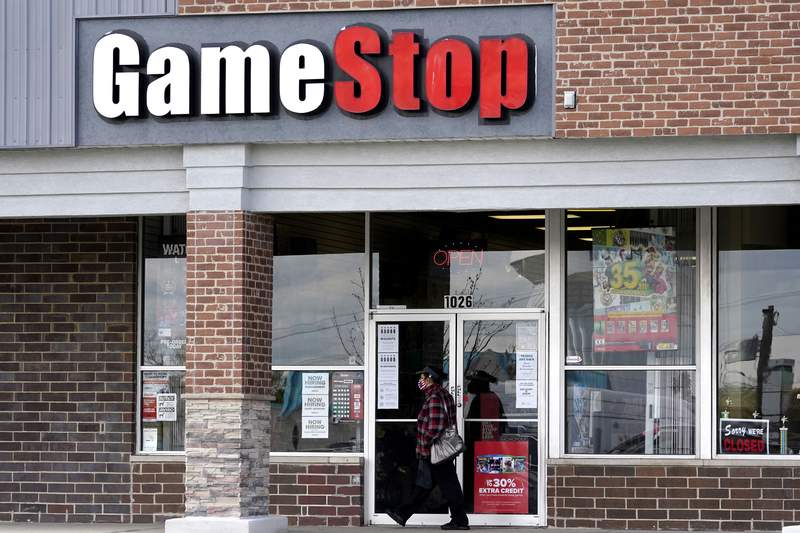 A woman wears a face mask as she walks past a GameStop store in Des Plaines, Ill., Thursday, Oct. 15, 2020. The latest battleground between the proletariat and the hedge funds serving the 1% isnt on just any street. Its on Wall Street. At least, thats the view within an army of smaller-pocketed, optimistic investors who are throwing dollars and buy orders at the stock of video-game retailer GameStop. (AP Photo/Nam Y. Huh, file)