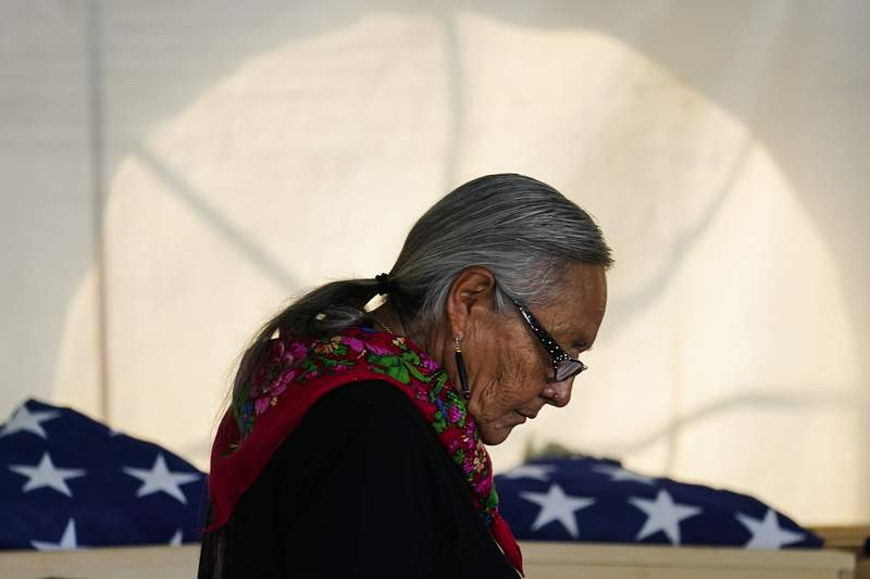 Ione Quigley, the Rosebud Sioux's historic preservation officer, returns to her seat after speaking during a ceremony at the U.S. Army's Carlisle Barracks, in Carlisle, Pa., Wednesday, July 14, 2021. The disinterred remains of nine Native American children who died more than a century ago while attending a government-run school in Pennsylvania were headed home to Rosebud Sioux tribal lands in South Dakota on Wednesday after a ceremony returning them to relatives. (AP Photo/Matt Rourke)