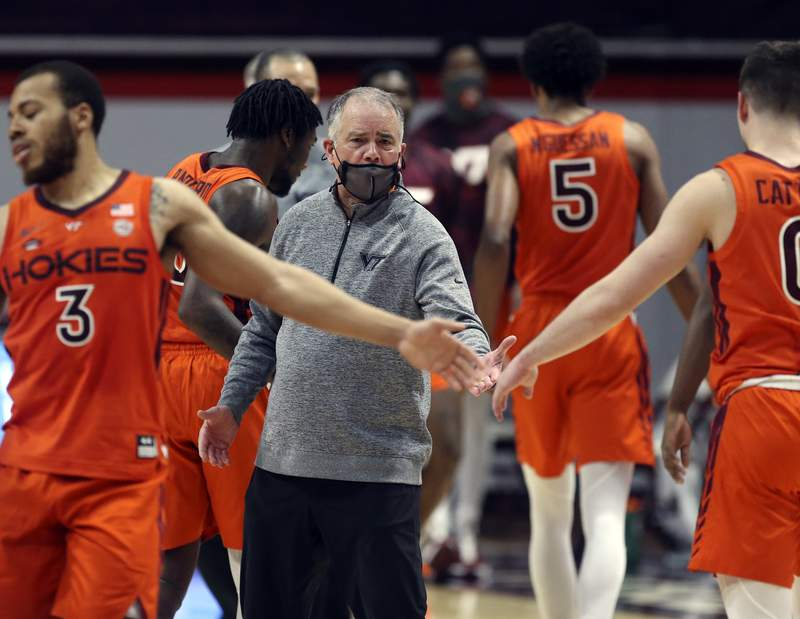 Virginia Tech head coach Mike Young celebrates with his team after a score during the second half of an NCAA college basketball game in Blacksburg Va. Saturday February 27 2021. (AP Photo /  MATT GENRTY, The Roanoke Times, Pool)