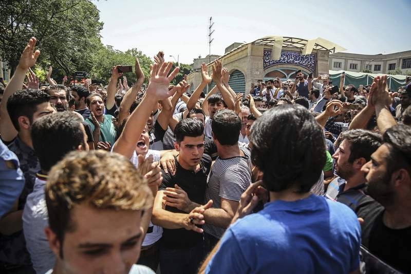 FILE - In this June 25, 2018 file photo, a group of protesters chant slogans at the main gate of the Old Grand Bazaar, in Tehran, Iran. On Saturday, Sept. 5, 2020, Iran broadcast the televised confession of a wrestler facing the death penalty after a tweet from President Donald Trump criticizing the case, a segment that resembled hundreds of other suspected coerced confessions aired over the last decade in the Islamic Republic. The case of 27-year-old Navid Afkari has drawn the attention of a social media campaign that portrays him and his brothers as victims targeted over participating in protests against Iran's Shiite theocracy in 2018. (Iranian Labor News Agency via AP, File)