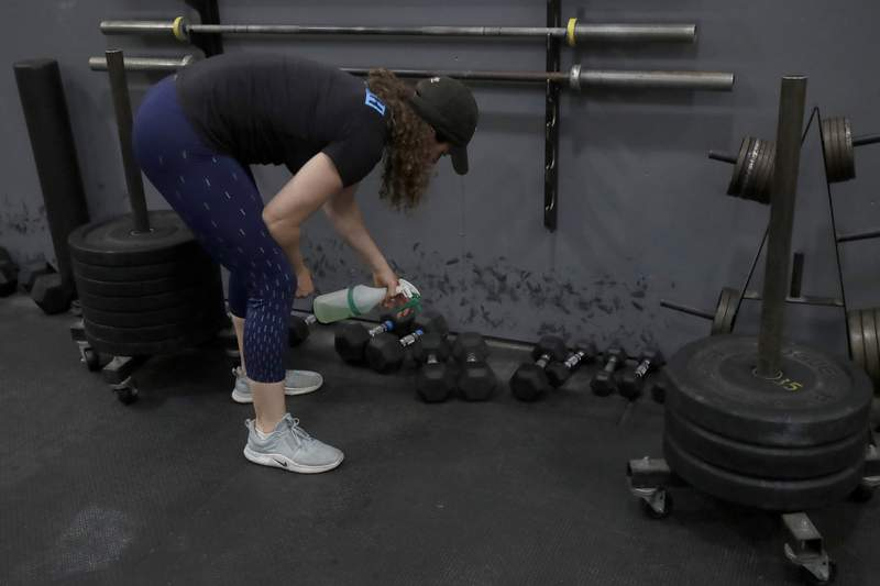 FILE - In a  Friday, April 24, 2020 file photo, Alexis Garrod, CrossFit Potrero Hill partner and head coach, cleans off weight training equipment in an empty gym, which closed for shelter in place orders over COVID-19 concerns, in San Francisco. Reebok says it has cut ties with CrossFit chief executive and founder invoked George Floyds name in a Twitter post chastising a health group for saying that racism was a public health problem. (AP Photo/Jeff Chiu, File)