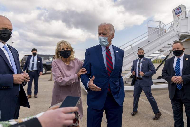 Jill Biden moves her husband, Democratic presidential candidate former Vice President Joe Biden, back from members of the media as he speaks outside his campaign plane in New Castle, Del., on Oct. 5, 2020. (AP Photo/Andrew Harnik)