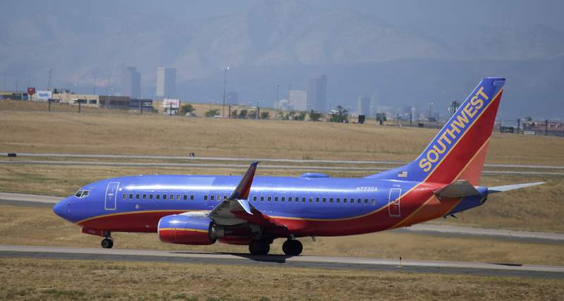 With the city skyline in the background, a Southwest Airlines jetliner taxis to the west runway for takeoff from Denver International Airport, Tuesday, Aug. 24, 2021, in Denver. The pilots union is suing Southwest Airlines, saying that rules the airline put into place before and during the pandemic have changed pay rates and working rules, in violation of federal labor law. (AP Photo/David Zalubowski)