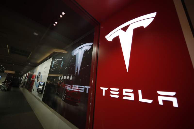 FILE - This Feb. 9, 2019, file photo shows a sign bearing the company logo outside a Tesla store in Cherry Creek Mall in Denver.  The U.S. government's road safety agency has added another fatality, Friday, Sept. 3, 2021,  involving a Tesla to the list of crashes it is probing due to the use of partially automated driving systems. (AP Photo/David Zalubowski, File)