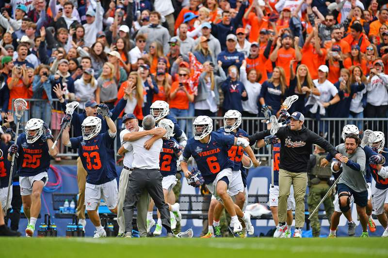 EAST HARTFORD, CT - MAY 31: Virginia Cavaliers head coach Lars Tiffany embraces assistant Brian Wilberger as the players race onto the field to celebrate their win over Maryland Terrapins during the Division I Men's Lacrosse Championship held at Pratt and Whitney Stadium at Rentschler Field on May 31, 2021 in East Hartford, Connecticut. The defending champion Cavaliers repeated their title with the 17-16 win over the Terrapins. (Photo by Larry French/NCAA Photos via Getty Images)