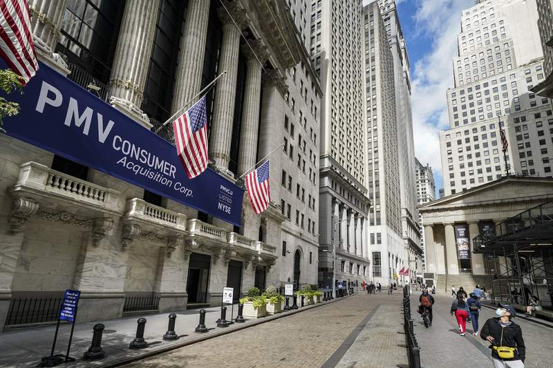 Pedestrians pass the New York Stock Exchange, Friday, Oct. 2, 2020, in New York.   Stocks are rising on Wall Street Friday as talks appear to be continuing in the start-and-stop drive on Capitol Hill to deliver more aid to the ailing economy.  (AP Photo/John Minchillo)