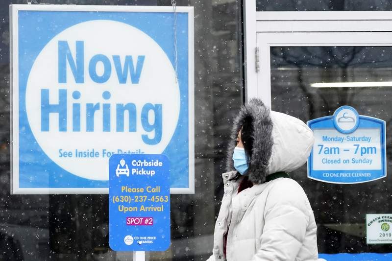"""FILE - In this Feb. 6, 2021 file photo, a woman walks past a """"Now Hiring"""" sign displayed at a CD One Price Cleaners in Schaumburg, Ill.  In a stark sign of the economic inequality that has marked the pandemic recession and recovery, Americans as a whole are now earning the same amount of wages and salaries that they did before the pandemic struck, even with nearly 9 million fewer people at work.  (AP Photo/Nam Y. Huh, File)"""