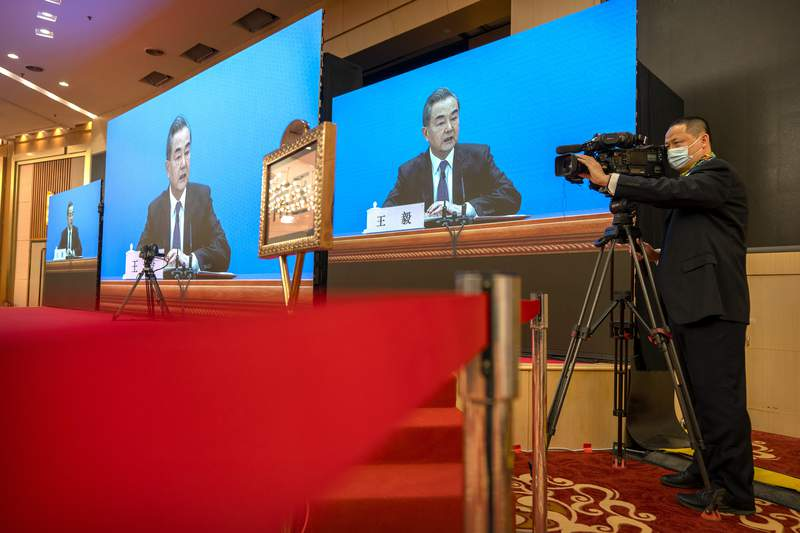 Chinese Foreign Minister Wang Yi speaks during a remote video press conference held on the sidelines of the annual meeting of China's National People's Congress (NPC) in Beijing, Sunday, March 7, 2021. (AP Photo/Mark Schiefelbein)