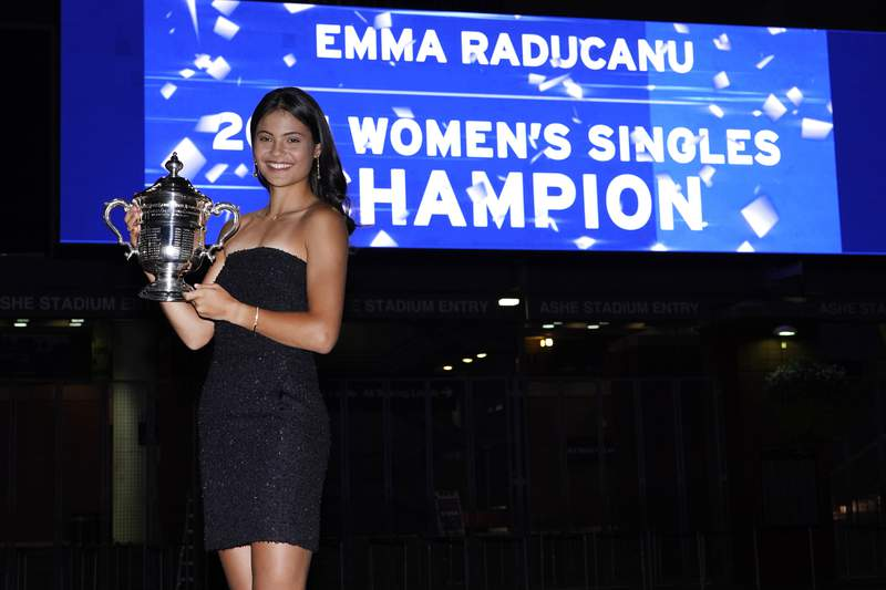 Emma Raducanu, of Britain, poses outside Arthur Ashe Stadium with the championship trophy after she defeated Leylah Fernandez, of Canada, in the women's singles final of the US Open tennis championships, Saturday, Sept. 11, 2021, in New York. (AP Photo/Elise Amendola)