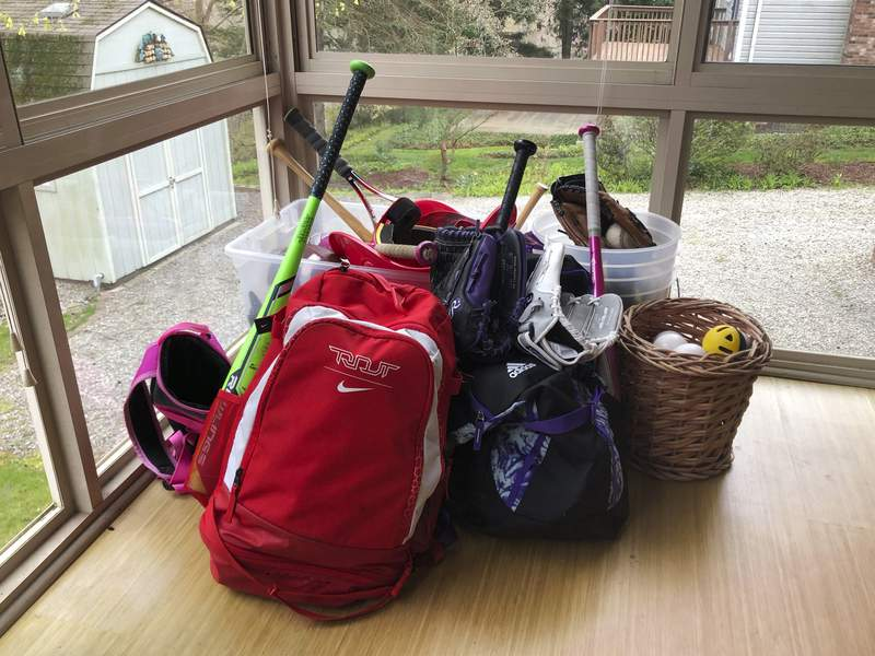 In this April 14, 2020, photo, baseball and softball bags for Colin and Catherine Graves lie untouched in Monroeville, Pa. The spring seasons for both children's youth leagues are on hold and in danger of being canceled due to the COVID-19 pandemic. (AP Photo/Will Graves)