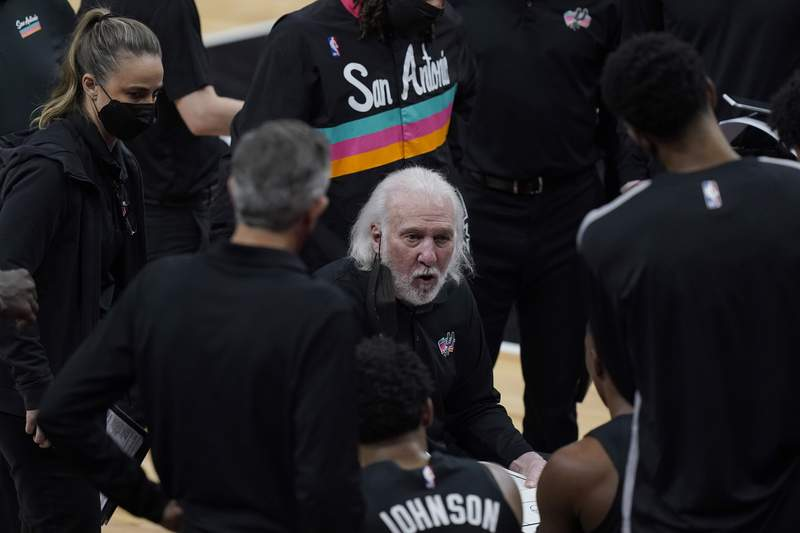 San Antonio Spurs head coach Gregg Popovich, center, talks to his players during a timeout in the first half of an NBA basketball game against the Phoenix Suns in San Antonio, Sunday, May 16, 2021. (AP Photo/Eric Gay)