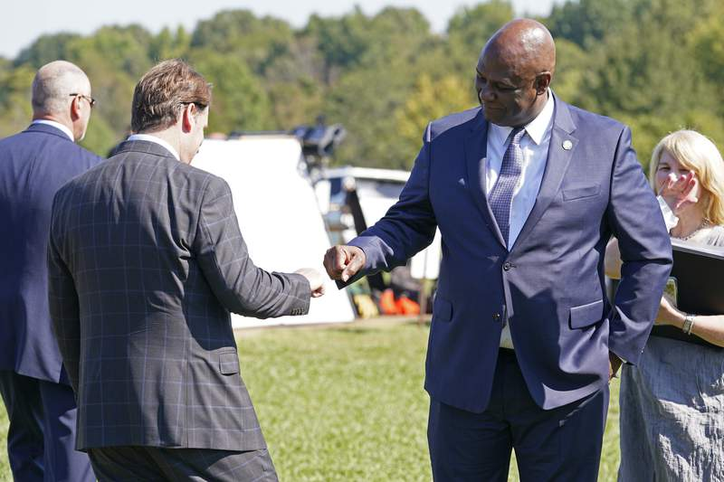 United Auto Workers President Ray Curry, right, bumps fists with Jim Farley, Ford president and CEO, left, after a presentation on the planned factory to build electric F-Series trucks and the batteries to power future electric Ford and Lincoln vehicles Tuesday, Sept. 28, 2021, in Memphis, Tenn. The plant in Tennessee is to be built near Stanton, Tenn. (AP Photo/Mark Humphrey)