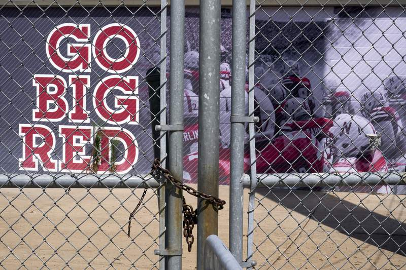 Gates leading into Memorial Stadium are padlocked, in Lincoln, Neb., Wednesday, Aug. 12, 2020. The Big Ten won't play football this fall because of concerns about COVID-19, becoming the first of college sports' power conferences to yield to the pandemic. The move was announced Tuesday. (AP Photo/Nati Harnik)