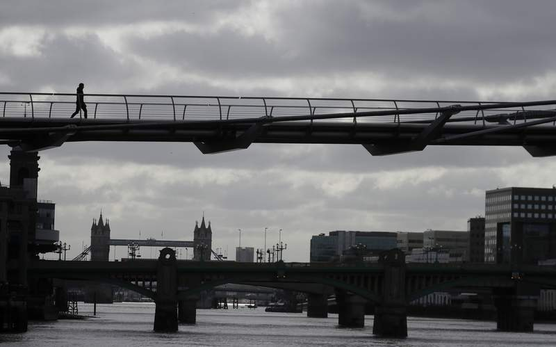 FILE - In this Monday, May 11, 2020 file photo, a pedestrian walks across the Millennium Bridge over the river Thames in London, during the morning rush hour as the lockdown continues to help stop the spread of coronavirus. White collar staff reaping the financial benefits of working from home should be taxed to help other workers who aren't getting the same advantages, experts at Deutsche Bank said in a new report on Tuesday Nov. 10, 2020. (AP Photo/Kirsty Wigglesworth, File)