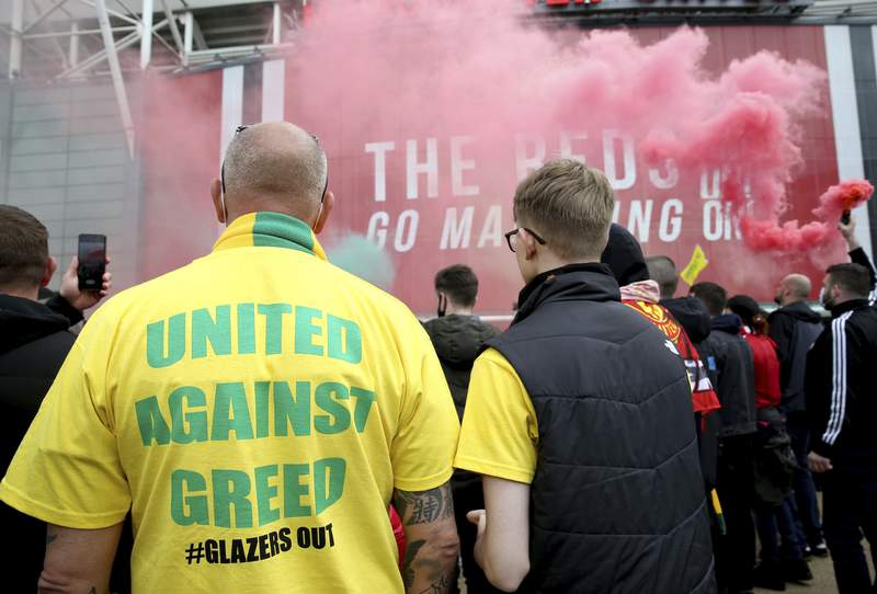 "A fan wears a shirt with a ""United Against Greed"" message, as fans gather to protest against the Glazer family, the owners of Manchester United, outside Old Trafford stadium, in Manchester, England, before their English Premier League match against Liverpool, Sunday, May 2, 2021. Manchester United supporters have stormed into the stadium and onto the pitch ahead of Sunday's game against Liverpool as fans gathered outside Old Trafford to protest against the Glazer ownership. (Barrington Coombs/PA via AP)"
