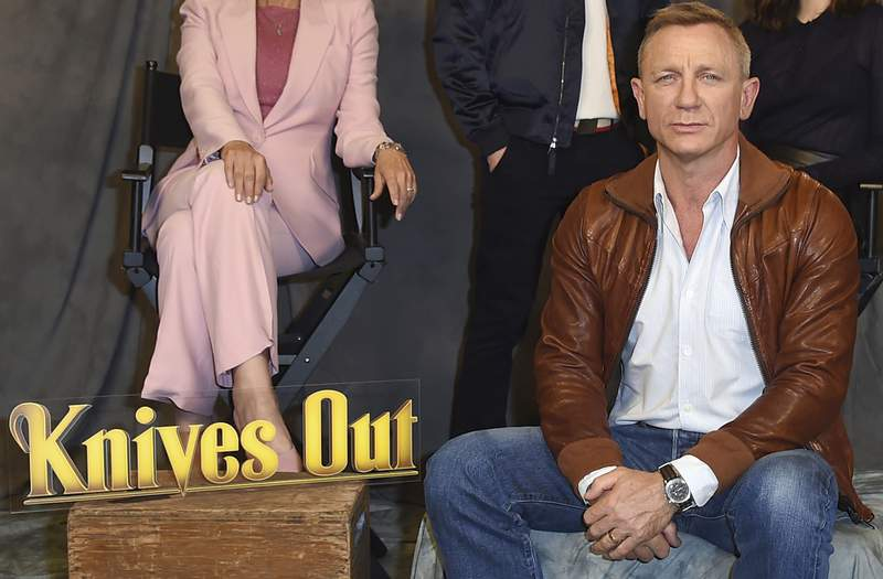 """FILE - Daniel Craig attends the """"Knives Out"""" photo call on Nov. 15, 2019, in Los Angeles. Netflix said Wednesday, March 31, 2021, it has reached a deal for two sequels to Rian Johnson's acclaimed 2019 whodunit, """"Knives Out."""" Johnson will direct with Daniel Craig returning as inspector Benoit Blanc. (Photo by Jordan Strauss/Invision/AP, File)"""