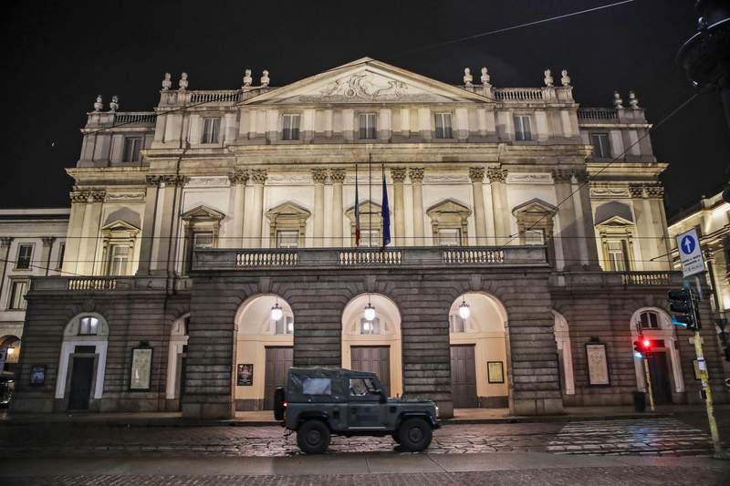 FILE - In this early Sunday, Oct. 25, 2020 file photo, A military vehicle drives past La Scala opera theater in Milan, northern Italy. The number of performers at Milans famed La Scala opera house positive with the coronavirus has risen to 21, even as the theater was forced to close due to new government restrictions aimed at curbing the virus resurgence. La Scala spokesman Paolo Besana confirmed Tuesday that 18 members of the world-class chorus and  three woodwind players in the orchestra have the virus. That comes after two singers, including tenor Francesco Meli, tested positive, ahead of planned concert performances last week of Aida.(AP Photo/Luca Bruno, File)
