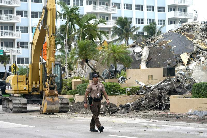 A police officer walks past the collapsed and demolished Champlain Towers South condominium building, Tuesday, July 6, 2021, in Surfside, Fla. (AP Photo/Lynne Sladky)