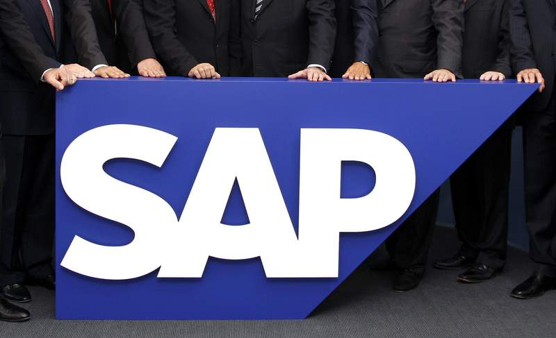 FILE - In this July 31, 2008 file picture the board members of German software company SAP stand behind the company logo at its headquarters in Walldorf near Heidelberg, southwestern Germany.  U.S. prosecutors said Thursday, April 29, 2021,  that software giant SAP will have to pay $8 million in penalties in acknowledging allegations that it illegally exported its products to Iran. The U.S. said the German company would have faced stiffer penalties had it not voluntarily disclosed the activities that violated American sanctions against Iran.  (AP Photo/Daniel Roland,File)