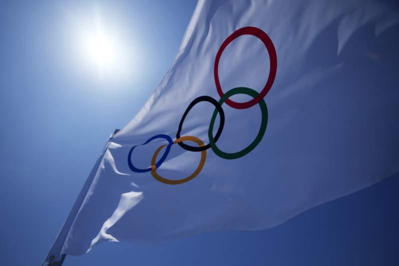 An Olympic flag flies over the top of the bleachers at Ariake Tennis Center, Monday, July 19, 2021, in Tokyo. (AP Photo/Kiichiro Sato)