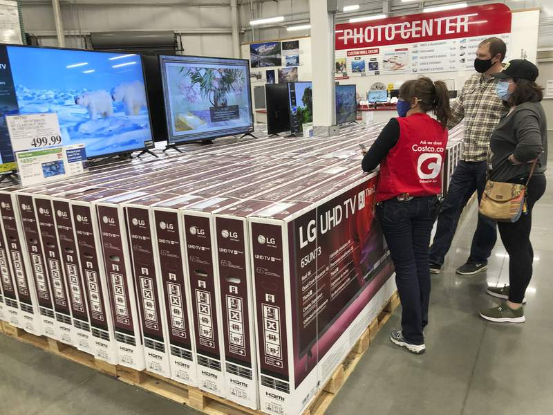 A sales associate helps customers as they consider the purchase of a big-screen television at a Costco warehouse on Wednesday, Nov. 18, 2020, in Sheridan, Colo.  U.S. consumer confidence fell to a reading of 96.1 in November as rising coronavirus cases pushed Americans confidence down to the lowest level since August. The Conference Board said the November reading represented a drop from a revised 101.4 in October.  (AP Photo/David Zalubowski)