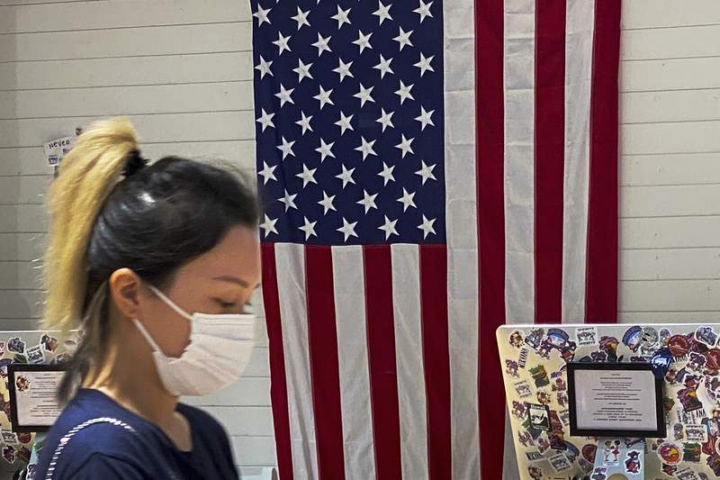 """A woman wearing a face mask walks by a counter displaying an American flag at a fashion boutique in Beijing, Sunday, July 11, 2021. China on Sunday said it will take """"necessary measures"""" to respond to the U.S. blacklisting of Chinese companies over their alleged role in abuses of Uyghur people and other Muslim ethnic minorities. (AP Photo/Andy Wong)"""