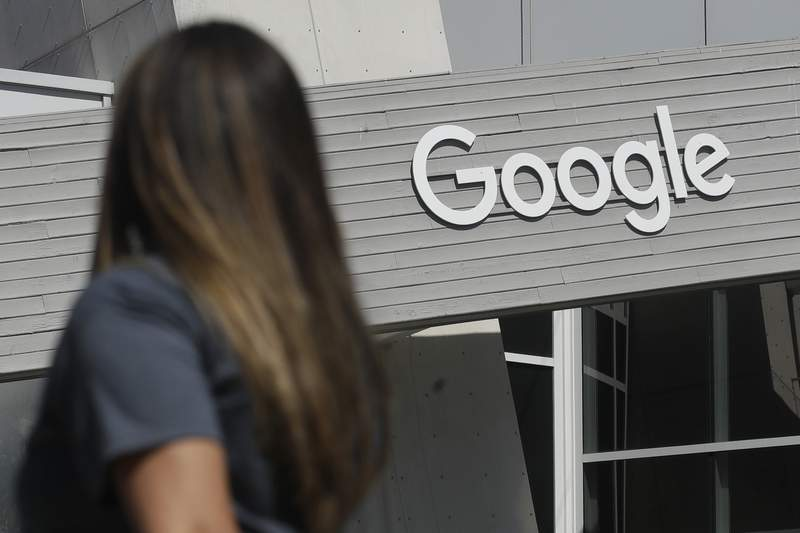 FILE - In this Sept. 24, 2019, file photo, a woman walks below a Google sign on the campus in Mountain View, Calif. Google is in the crosshairs of U.S. antitrust regulators who accuse it of wrongdoing similar to charges Microsoft faced 22 years ago, when Google was starting out in a Silicon Valley garage. How Google grew from its idealistic roots into what regulators describe as a cutthroat behemoth is a story shaped by unbridled ambition, savvy decision making, technologys networking effects, lax regulatory oversight and the pressure to pump up profits. (AP Photo/Jeff Chiu, File)