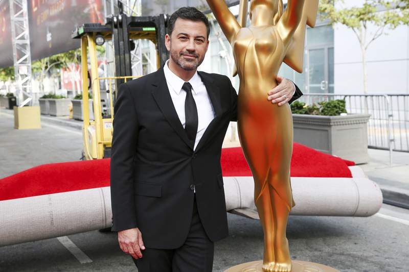 FILE - This Sept. 14, 2016 file photo shows host Jimmy Kimmel posing for a photo with a replica of an Emmy statue at the Primetime Emmy Awards Press Preview Day in Los Angeles. Kimmel will return as host and will serve as executive producer for the 72nd Emmy Awards. The show will be broadcast, Sunday, Sept. 20, on ABC. (Photo by Rich Fury/Invision/AP, File)