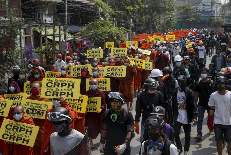 Buddhist monks, supporters of anti-coup protesters display placards with the letters CRPH standing for Committee Representing elected members of the Union Parliament from the National League for Democracy Party, during a street march in Mandalay, Myanmar, Wednesday, March 10, 2021. (AP Photo)