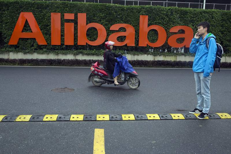FILE - In this May 27, 2016, file photo, a man talks on his phone as a woman rides on an electric bike past a company logo at the Alibaba Group headquarters in Hangzhou in eastern China's Zhejiang province. Chinas largest e-commerce company Alibaba said Monday, Aug. 9, 2021, that it fired the manager accused of sexual misconduct and pledged to strengthen its anti-sexual harassment policy after the female employee at the company accused the firm of suppressing her report of sexual assault. (AP Photo/Ng Han Guan, File)