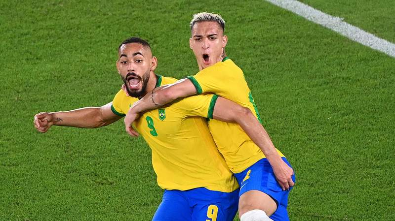 Matheus Cunha celebrates with Antony after scoring for Brazil against Spain during the Tokyo 2020 Olympic Games football competition men's gold medal match at Yokohama International Stadium.