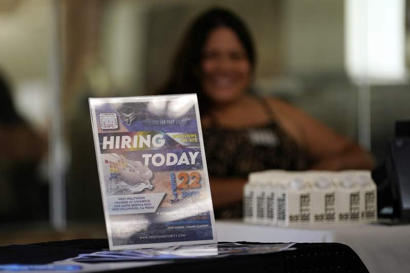 A hiring sign is placed at a booth for prospective employers during a job fair Wednesday, Sept. 22, 2021, in the West Hollywood section of Los Angeles.  The number of Americans applying for unemployment aid rose last week for a second straight week to 351,000, a sign that the delta variant of the coronavirus may be disrupting the job markets recovery, at least temporarily.(AP Photo/Marcio Jose Sanchez)