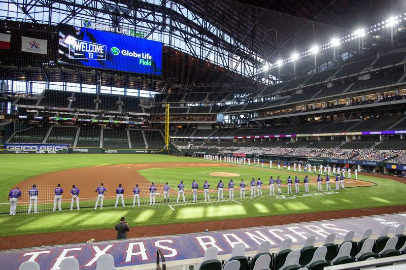 FILE - The Texas Rangers and Colorado Rockies line the foul lines of Globe Life Field before an opening day baseball game in Arlingtn, Texas, in this Friday, July 24, 2020, file photo. The Texas Rangers could have a full house for their home opener next month after debuting their new 40,518-seat stadium without fans in the stands for their games last season. If that happens, the Rangers could be the first team in MLB or any U.S.-based sport to have a full-capacity crowd since the coronavirus pandemic started rapidly shutting down sports a year ago this week. (AP Photo/Jeffrey McWhorter, File)