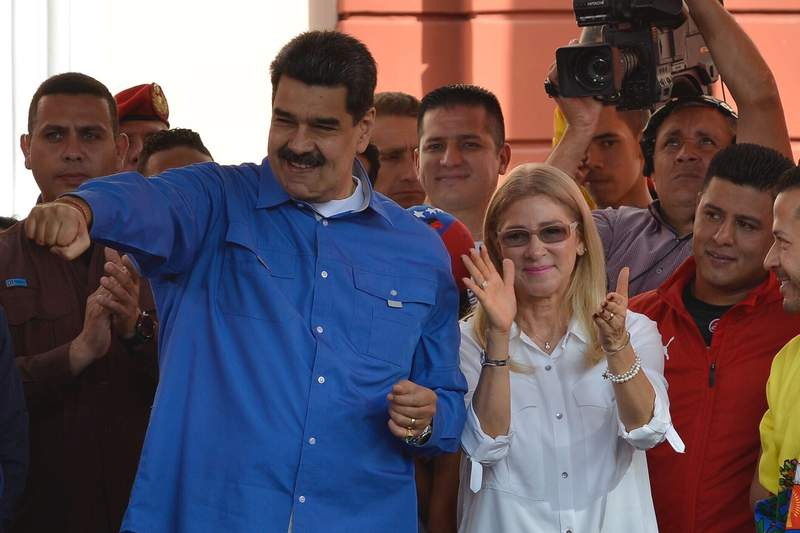 Venezuela's President Nicolas Maduro, accompanied by first lady Cilia Flores, greets supporters during an event at the Miraflores Presidential Palace to mark Youth Day, in Caracas, Venezuela, Wednesday, Feb. 12, 2020. (AP Photo/Matias Delacroix)